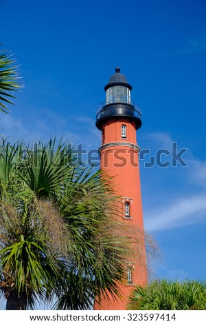 Vertical image of the tallest lighthouse in Florida and second tallest in the United States surrounded by palm trees in late afternoon light