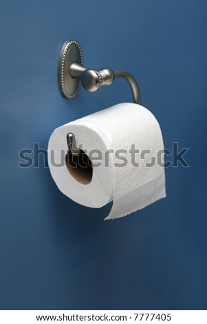 vertical image of toilet paper on blue wall, angled right - stock photo