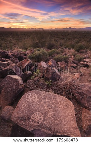 Vertical  landscape of sunset with petroglyphs drawing on a boulder - stock photo