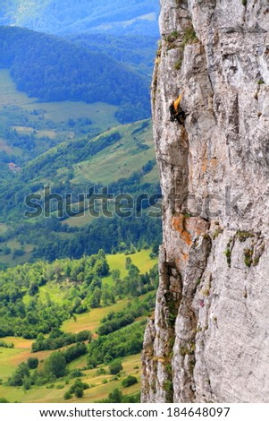 Vertical limestone wall and one climber high above ground