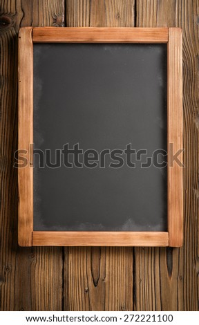 vertical old chalkboard board on aged dark wooden wall - stock photo