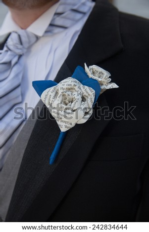 vertical orientation close up of a bearded man in a tuxedo wearing a unique, hand made, boutonniere made with paper flowers / Unique Boutonniere - stock photo