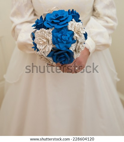 vertical orientation close up of a bride in a vintage wedding gown, holding a bouquet of hand made,  paper flowers in royal blue and off white printed paper, with copy space / Vintage Wedding Gown - stock photo