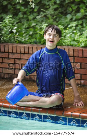 vertical orientation close up of a happy, smiling boy with autism and down's syndrome sitting cross legged at the edge of the pool with a bucket / Sensory Water Play - stock photo