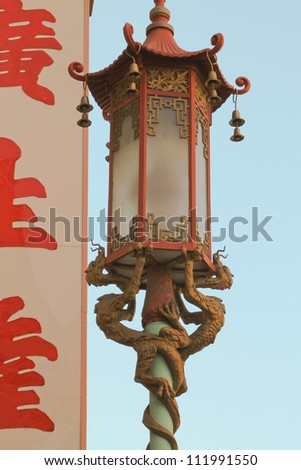 vertical orientation close up of a street lantern being supported by two dragons / Dragon Lantern Details - stock photo