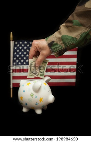vertical orientation close up of a woman's arm and hand in camouflage uniform putting cash in a piggy bank, with the U.S. flag in the background on isolated black / Saving while Serving - Vertical - stock photo