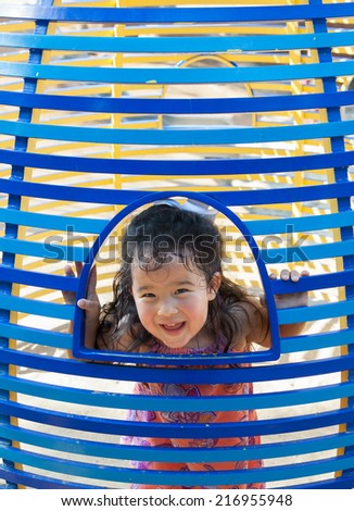 vertical orientation close up of an energetic, smiling, girl toddler peeking through a metal structure made with bands of light and royal blue / Peek a Boo through Painted Blue Metal - stock photo