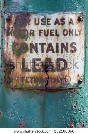 vertical orientation close up of vintage antique sign for leaded motor fuel with turquoise background and copy space / Fully Leaded Motor Fuel Vintage Sign - stock photo