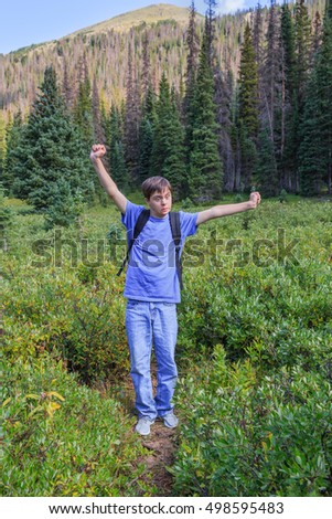 vertical orientation color image of a teenage boy with autism and down's syndrome in the Rocky Mountains, making a silly, scared face / I Can't Believe My Eyes!