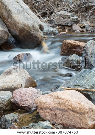 vertical orientation color image, taken with a very slow shutter speed to show the movement of water in a creek through a rocky landscape / Beautiful Rocky Mountain Creek