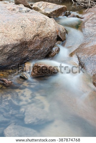 vertical orientation color image, taken with a very slow shutter speed to show the movement of water in a creek through a rocky landscape / Winter Waterfall - a Current Event - stock photo