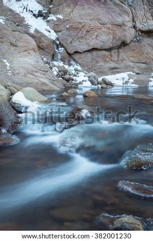 vertical orientation color image, taken with very slow shutter speed, showing water flowing in a creek in winter, with ice formations/ Colorado Creek in Winter Time - stock photo