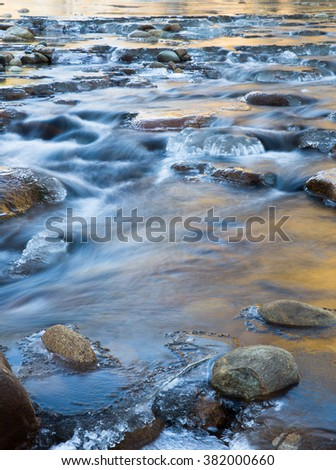 vertical orientation color image, taken with very slow shutter speed to show water flowing over rocks in a creek in Colorado / Flowing Water in an Icy Riverbed in Winter - stock photo