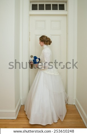vertical orientation color photo of a beautiful, young, bride, dressed in an antique vintage gown, standing at the interior doorway of a vintage building / Ready for Marriage - stock photo