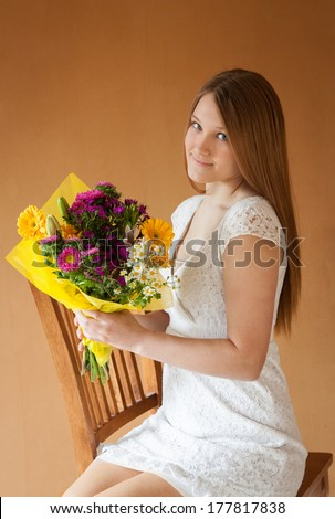 vertical orientation of a lovely, smiling, teenage girl in a white dress holding a colorful bouquet of flowers as she sits on a chair, with a warm, neutral background / Flowers say Congratulations - stock photo