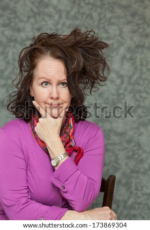 vertical orientation of a woman in brightly colored business attire with a questioning look on her face and a crazy hair style with neutral background / Time to Update my Style? - stock photo
