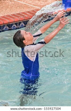 vertical orientation of boy with autism and down's syndrome outside in the pool playing with a bucket of water / Therapeutic Bucket Play - stock photo