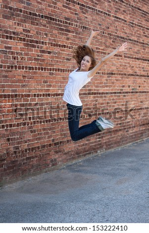vertical orientation of happy, beautiful,  teenage girl jumping for joy with vintage brick patterned background and copy space / Teenage Girl Jumping for Joy - stock photo