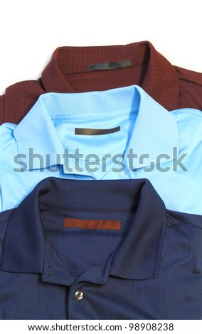 Vertical orientation shot of three golf shirts. Maroon, cyan, and navy blue. - stock photo