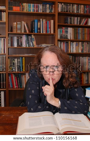 vertical orientation with shallow depth of field of a middle aged woman with glasses behind a table with books in the library hushing noisy patrons / QUIET!!! - stock photo