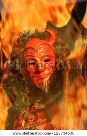 Vertical oriented image of red face devil with black hair among flames of fire.