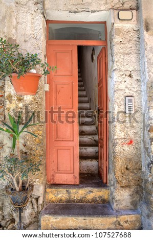 Vertical oriented image of wooden door and old narrow stairs in small house at town of Ventimiglia in Liguria, Italy. - stock photo