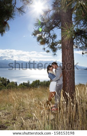 Vertical outdoor photo of young adult couple embracing in a grassy field above a lake. - stock photo
