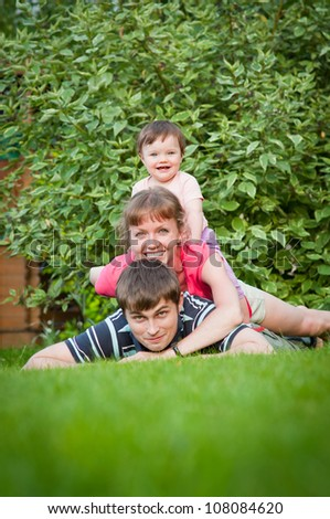 Vertical outdoor portrait of adorable young family with a baby girl