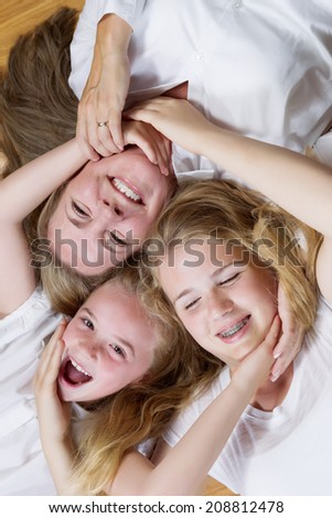 Vertical overhead view, facing forward, of mother and her daughters lying on oak wooden floor while all joining hands and faces together  - stock photo