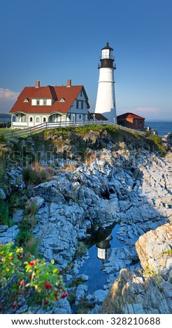Vertical panorama of the Portland Head Light, Portland, Maine, United States. The lighthouse is reflected in the rockpools below.  - stock photo