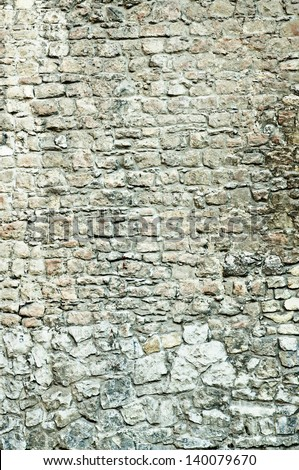 Vertical part of the antique old brick wall from grey stones (texture) - stock photo