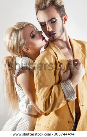 Vertical passionate photo of couple in love. Both with makeup. Studio shot. Gray background.