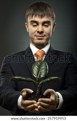 vertical photo  businessman in blue costume with  scion  rubber plant