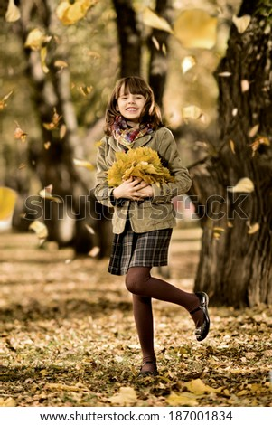 vertical photo,  happy beautiful little girl joyful  laughter with  autumnal  leaf, in park - stock photo