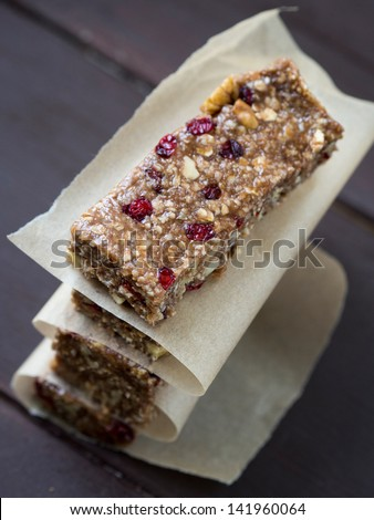 Vertical photo of a pile of homemade granola protein power bars with peanut butter, honey, nuts and cranberries, on a dark wooden background. Overhead view, close up. - stock photo