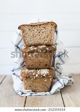 Vertical photo of a pile of three long rectangle homemade whole grain mixed rye-wheat sourdough breads with sunflower seeds and rolled oats. One bread cut in half, clear wooden background. - stock photo
