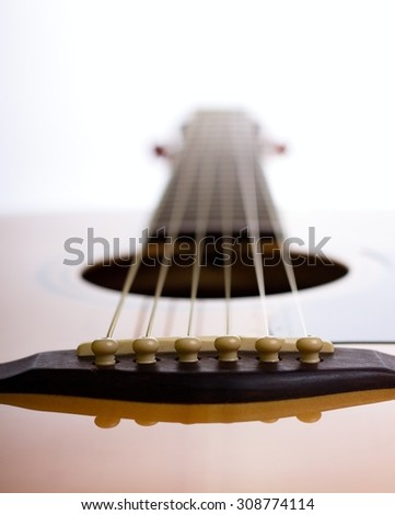 Vertical photo of an acoustic guitar bridge with six strings which are going against the backlight. The guitar is from solid spruce and wood of bridge is dark. - stock photo
