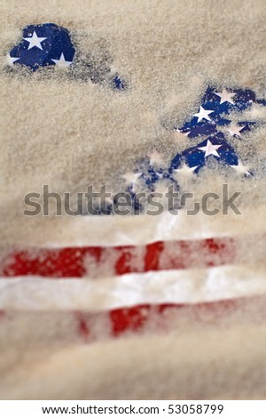 vertical photo of an american flag buried in sand - stock photo