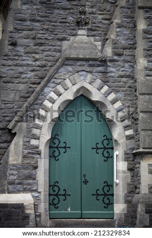 Vertical photo of an ancient green wooden door on a stone church in Carmarthen, Carmarthenshire, South West Wales.  It has an arched top and ornate black metal hinges. - stock photo