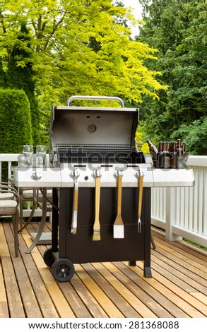 Vertical photo of an open barbecue cooker with cookware and cold beer in bucket on cedar wood patio. Table and colorful trees in background. - stock photo