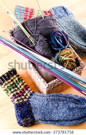 Vertical photo of box full of wool clues and several knitting needles and other accessories. Two pair of socks are around on wooden board.