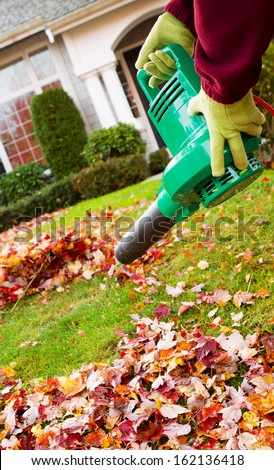 Vertical photo of electrical blower, gloved hands holding, cleaning leaves from front yard with house in background - stock photo