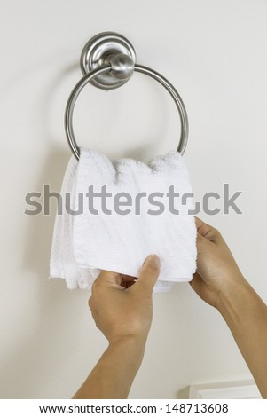 Vertical photo of female hands putting clean white towel on wall hook ring in bathroom  - stock photo