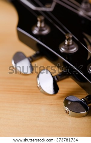 Vertical photo of guitar tuners on black head. Instrument is placed on light wooden board.