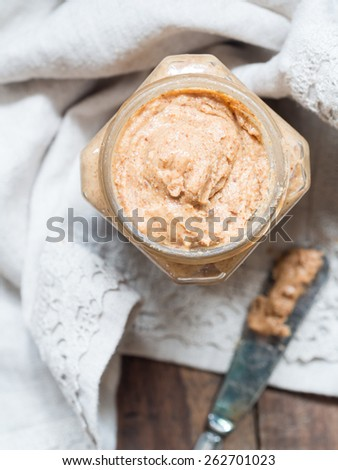 Vertical photo of homemade natural almond butter in a glass jar placed on rustic beige table cloth and with a butter knife on the side. Pastel colors. View from above.