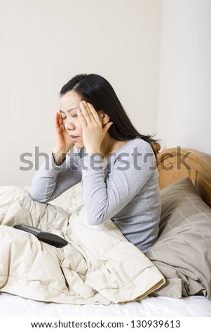 Vertical photo of mature woman, holding her head with both hands, while alarm clock is lying in bed
