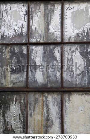 Vertical photo of old weathered rusted window boarded up with chipped and cracked grey panel
