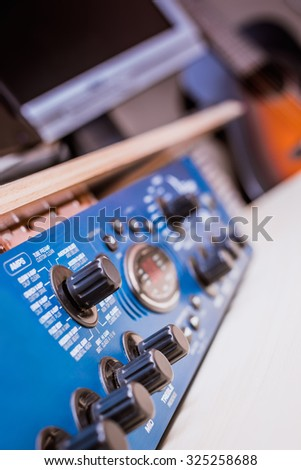 vertical photo of recording studio gears & acoustic guitar on background, focus to knob & shallow dept of field for studio music recording concept - stock photo