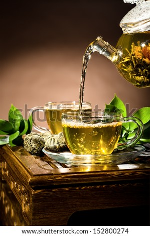 vertical photo, of the glass teapot flow green tea in cup on brown background,  tea ceremony - stock photo