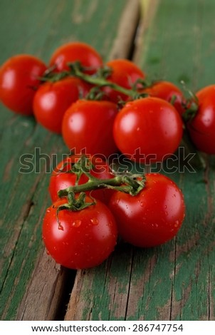Vertical photo of two brunches of juicy cherry red tomatoes with visible water drops on surface. Fruit is placed on old worn green table. - stock photo